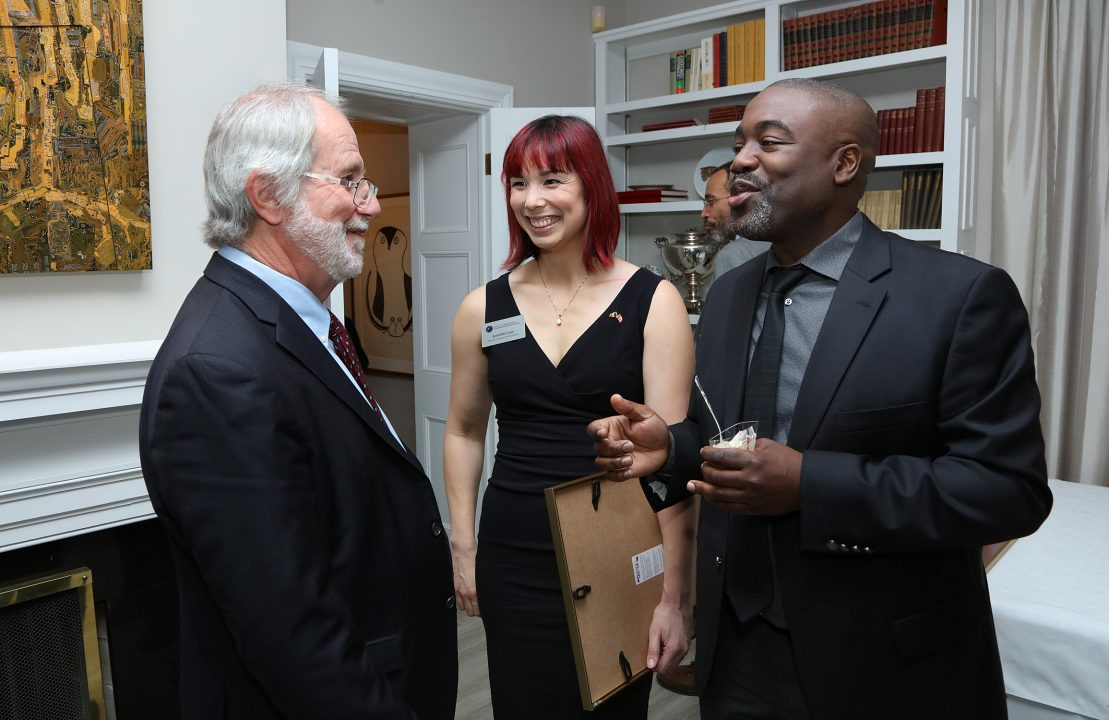 Queen's Principal Patrick Deane (left) speaks with Jennifer Low and Edward Nkole of the McDonald Insitute admin team.