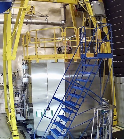 The detector is encased in silver stainless steel with bright yellow supports and walkways surrounding it. A blue staircase is in the foreground leading from the floor to the walkway on top of the detector.